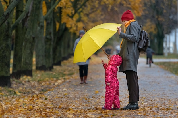 Small child stands in the yellow rain next to his mother in the park against the background of autumn yellow foliage.