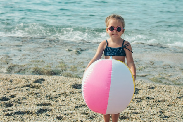 A small child in sunglasses plays with an inflatable ball on the sand. girl on the beach. summer vacation by the sea. travel to hot countries