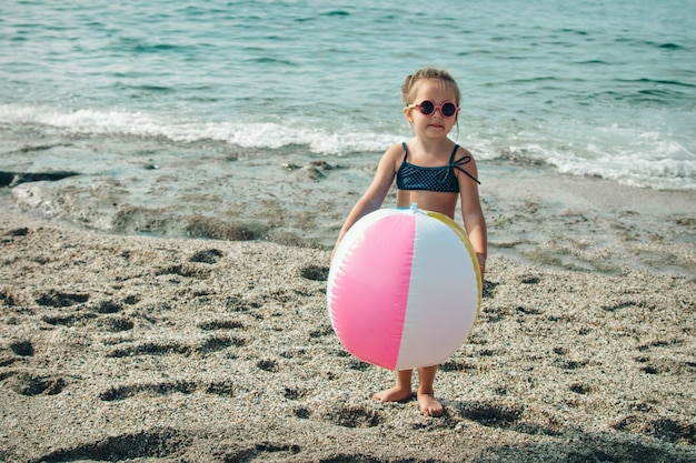 A small child in sunglasses plays with an inflatable ball on the sand.