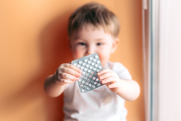A small child toddler baby boy holds a plate with pills in his hands selected focus on pills kid unfocused