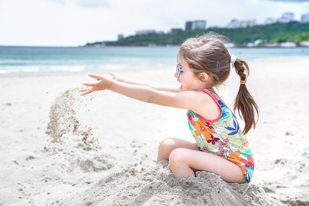 小さな子供が海岸の砂を投げます。夏の娯楽とレクリエーション。