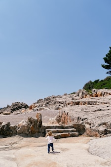 Small child walks along the rocky shore to the steps against the blue sky
