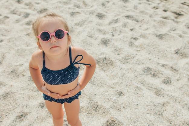 작은 아이는 해변에서 산책. 파란색 수영복과 여행에 둥근 안경 소녀