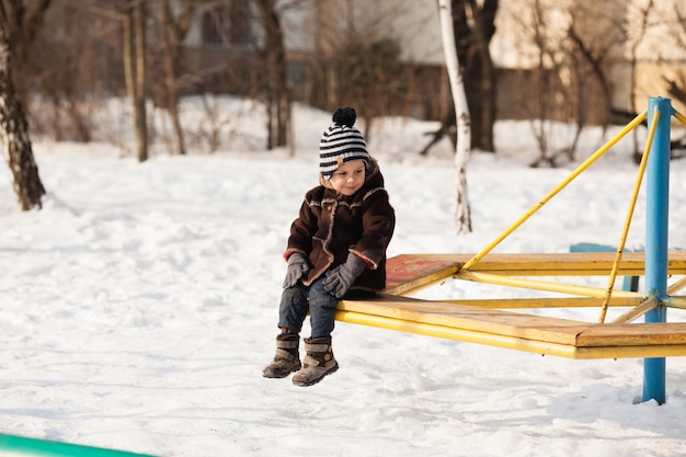 A small child in a warm brown jacket and hat playing on the playground in winter day