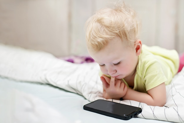 Small child watches cartoons on mobile phone lying on bed. girl using smartphone to play at home.