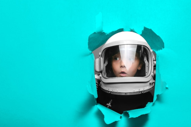 Small child in wearing an airplane helmet looking through a hole of colored paper