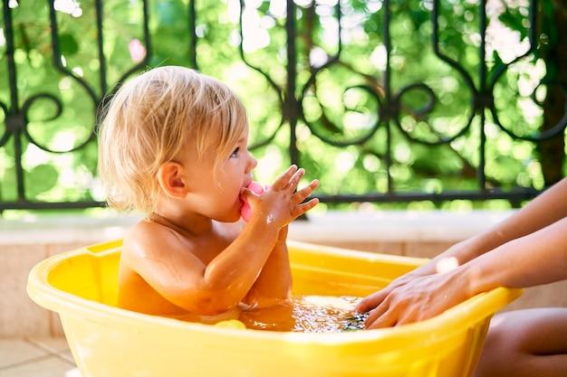 손에 장난감을 들고 있는 어린 아이가 발코니에 있는 물동이에 앉아 있다
