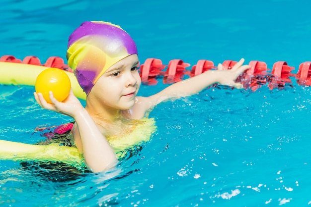 A small child with a life jacket on his chest is learning to swim in an indoor pool.