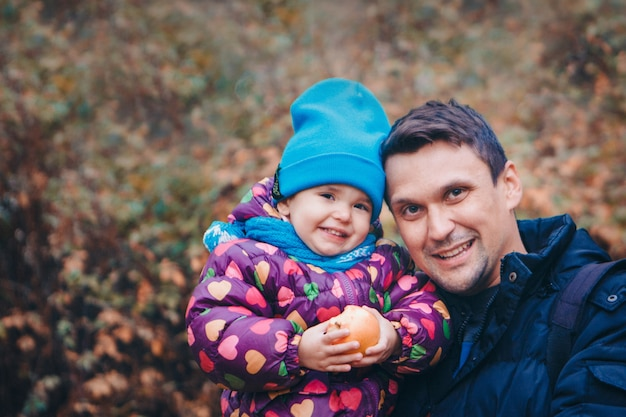 A small child with red apple with father in a warm suit walks in the woods. autumn park.  children's fashion, accessories, outdoor walks
