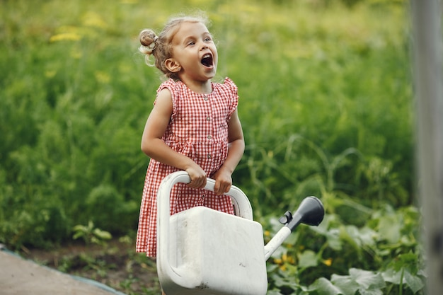 Small child with a watering can with flowers pour. girl with a funnel. child in a pink dress.