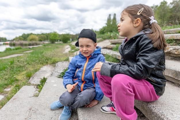 Маленькие дети что-то обсуждают, вместе сидят на природе.