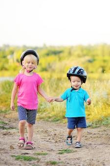 Маленькие дети-мальчик и девочка, брат и сестра в велосипедных шлемах держатся за руки на поверхности природы и улыбаются