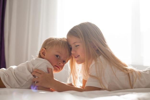 白いtシャツを着た小さな子供たちの兄と妹がベッドに横たわってお互いを見ています