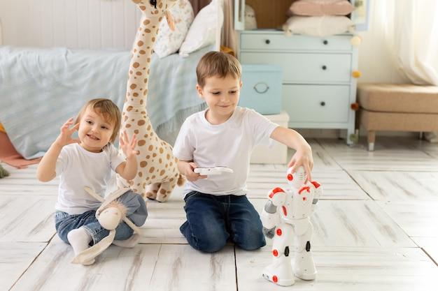 小さな子供たちの兄と妹が部屋の床に座って、笑ってロボットで遊んでいます