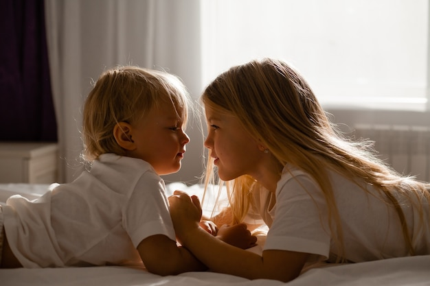 Small children brother and sister are lying on the bed and looking at each other