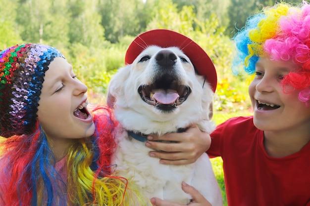 小さな子供たちは犬と一緒にエレガントなお祝いの楽しいかつらに身を包み、自然の中でそれで遊ぶ
