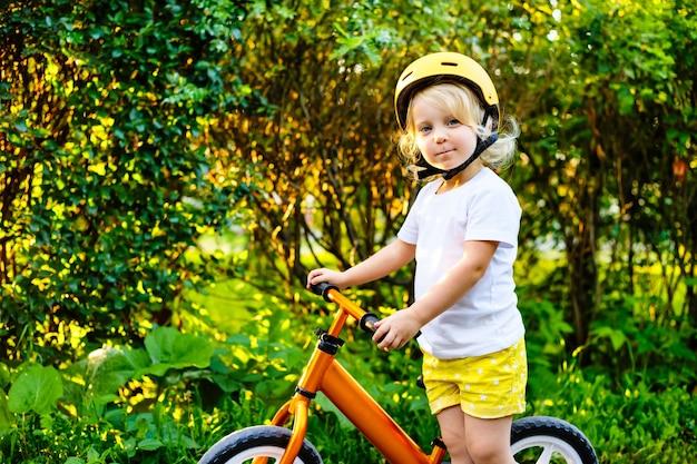 ヘルメットとバランスバイク屋外で遊ぶ小さな子供の女の子