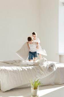 작은 아이들은 침대에서 점프하고 햇빛에 베개와 싸우는 재미.
