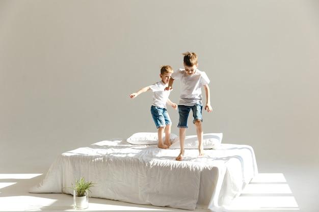 작은 아이들은 침대에서 점프하고 햇빛에 재미.