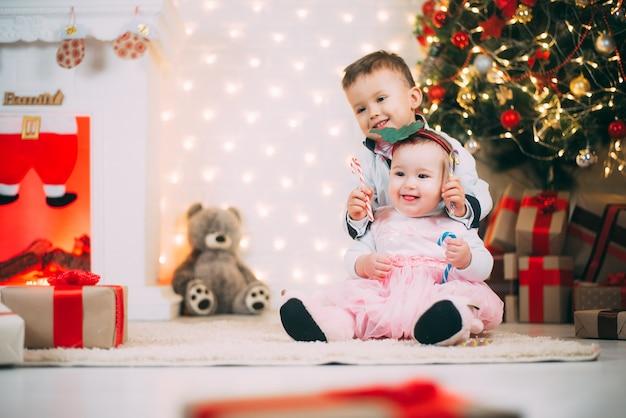 Маленькие дети возле елки и камина с цветными конфетами в руках