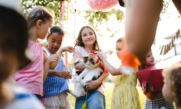 Small children outdoors in garden in summer, holding present pet cat. a celebration concept.