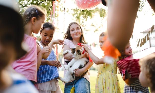 Маленькие дети на открытом воздухе в саду летом, держа настоящую домашнюю кошку. концепция празднования.
