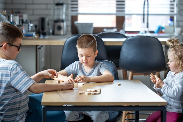Маленькие дети играют дома на кухне в настольную игру с деревянными кубиками.