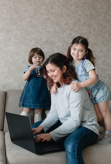 Small children prevent their mother from working on the computer. remote work at home