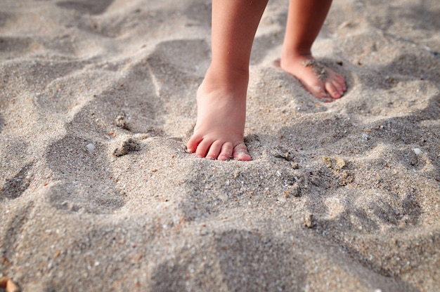 Small children's feet on the sandy beach in summer.