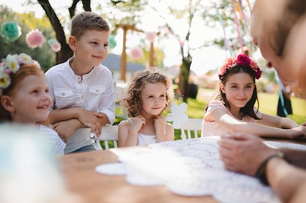 夏のガーデンパーティーで屋外のテーブルに座って話している小さな子供たち。