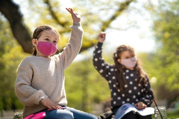 都市公園で屋外に座って、グループ教育とコロナウイルスの概念を学ぶ小さな子供たち。