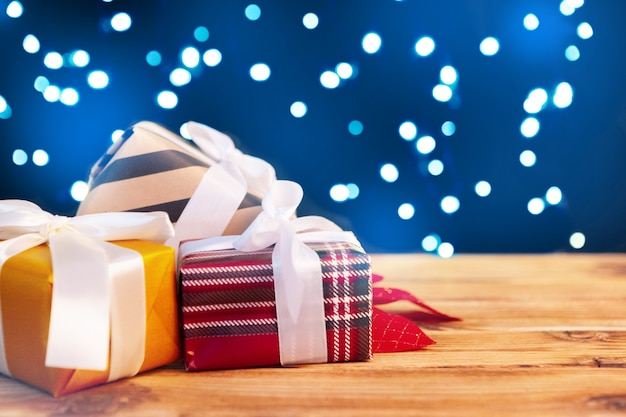 Small christmas gift boxes on wooden table against bokeh lights background