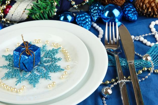 青いトーンのクローズアップでクリスマステーブルを提供するプレート上の小さなクリスマスプレゼント