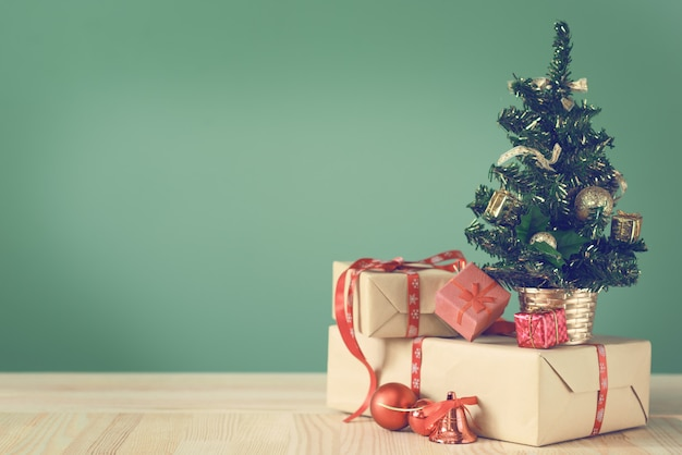 Small christmas tree and boxes with gifts on a wooden table.