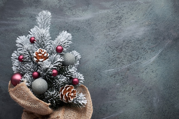 Small christmas tree in sackcloth decorated with red baubles and berries on dark