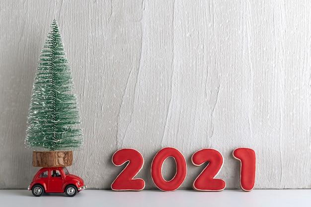 2021年の看板の横にあるおもちゃの車の上に小さなクリスマスツリーが立っています。スペースをコピーします。