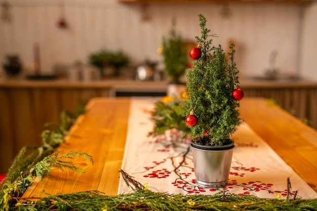 A small christmas tree with red balls in a metal bucket stands on a wooden table in the decorated kitchen.