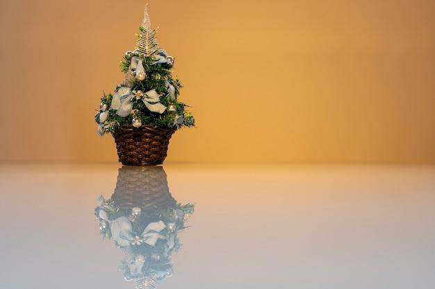 흰색 유리 테이블에 반사된 작은 크리스마스 트리