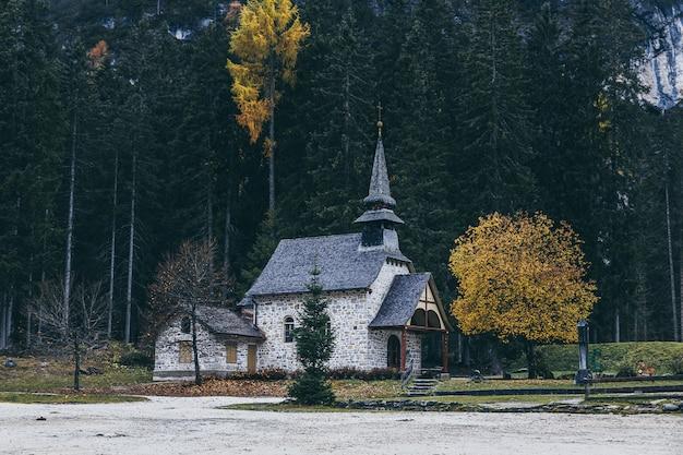 Small church near famous lake braies in italian alps in autumn season