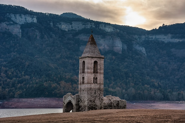 Small church in ruins with its bell-tower in front of mountains & beside a river at catalonia, spain
