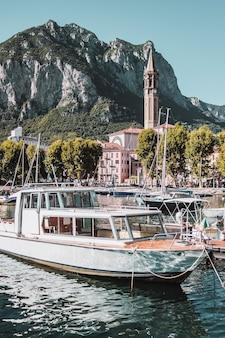 イタリアの山の風景のコモ湖の海岸に桟橋とボートのある小さな街
