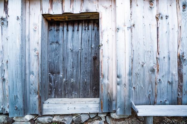 珍しい模様の古い家の美しい木製の壁にある小さな閉じたドア
