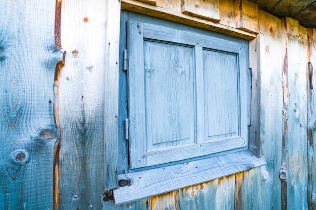 오래된 집의 나무 벽에 있는 작은 닫힌 창