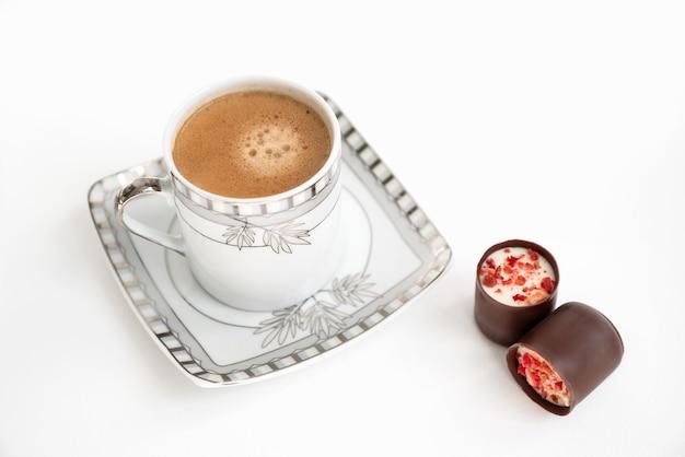 Маленькая кофейная чашка, наполненная эспрессо на квадратной тарелке и две шоколадные конфеты с фруктовой посыпкой сверху на белой поверхности