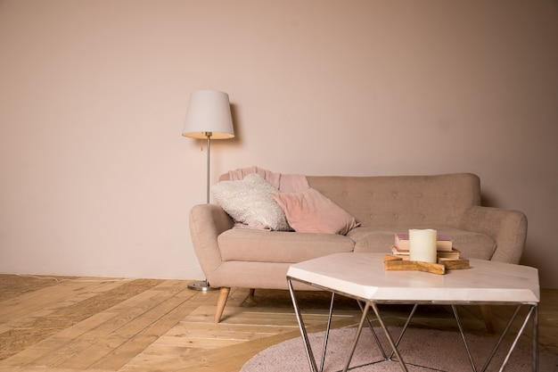 Small coffee table and candles next to designed sofa with pastel colored pillows