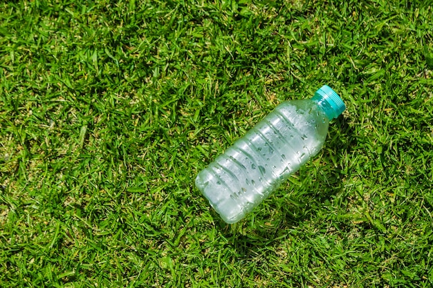 Small cold water bottle laying on green grassy field on a hot sunny day with room