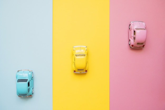 Small color toy cars on a yellow, pink and blue. racing to the finish line