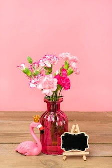 Small colored pink carnations in vase, frame, figure of flamingo on wooden table and pink wall