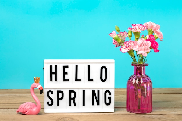 Small colored pink carnations in vase and lightbox with text hello spring, flamingo figure on white wooden table and blue wall holiday card seasonal concept