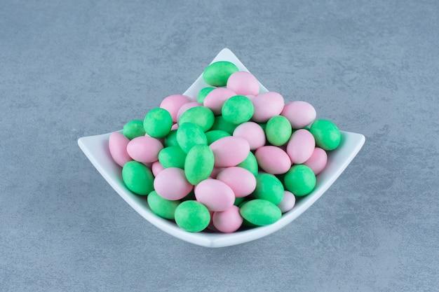 ボウルの中の大理石のテーブルの上にある小さなカラフルなチョコレート。